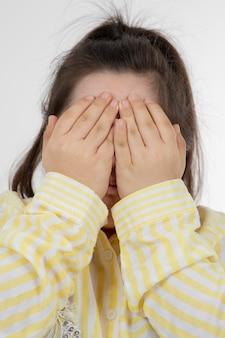 노란색 체크 무늬 셔츠를 입고 다운 증후군을 앓고있는 어린 소녀의 사진과 손으로 얼굴을 코닝