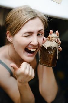 完璧な肌を持つ少女の写真。スキンクリームの小さな瓶を保持している笑顔の女性
