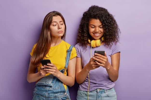 그들의 전화와 함께 포즈를 취하는 젊은 여자 친구의 사진
