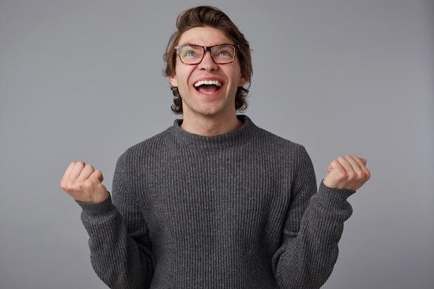 灰色のセーターを着て、灰色の背景の上に立っている眼鏡をかけた若い嬉しい男の写真。広く笑顔で拳を握りしめ、百万を勝ち取り、幸せを感じます。