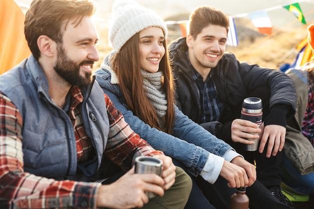 Фотография молодой группы друзей на улице в бесплатном альтернативном кемпинге над горами, пьющих горячий чай и разговаривающих друг с другом.