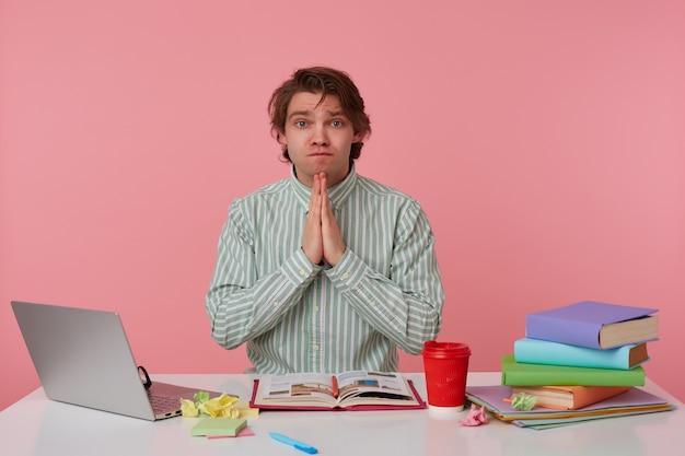 眼鏡をかけた若い男の写真、本を持ってテーブルに座って、ラップトップで作業し、祈りのジェスチャーでカメラを嘆き悲しんで見ている、ピンクの背景の上に隔離。