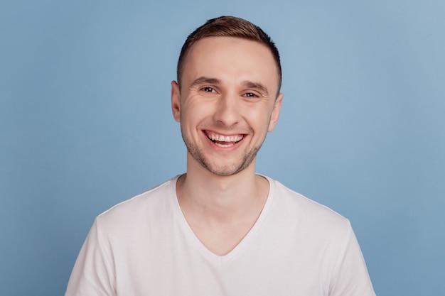 Фото молодого красивого прохладного человека, счастливого позитивного улыбки, веселого зубастого человека, изолированного на синем цветном фоне