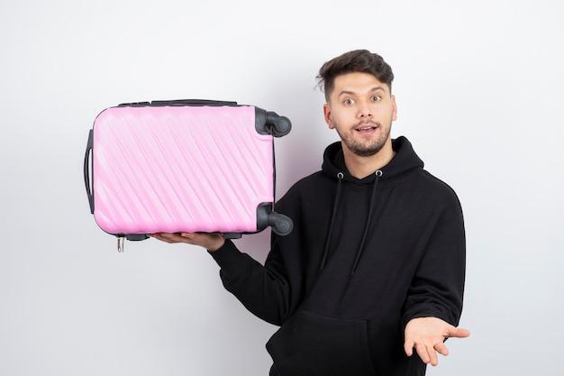 핑크 여행 가방을 들고 젊은 잘 생긴 남자 모델의 사진
