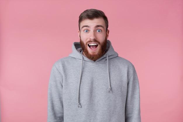 灰色のパーカーを着た若いハンサムな幸せな驚きの赤いひげを生やした男の写真は、驚いたように見え、大きく開いた口と目をピンクの背景の上に立っています。