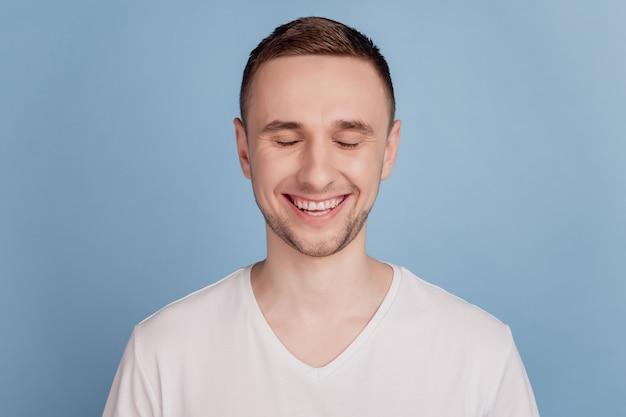 Фотография молодого красивого мужчины счастливой позитивной улыбкой с закрытыми глазами мечтает веселая зубастая изолированная над синим цветом backgrund