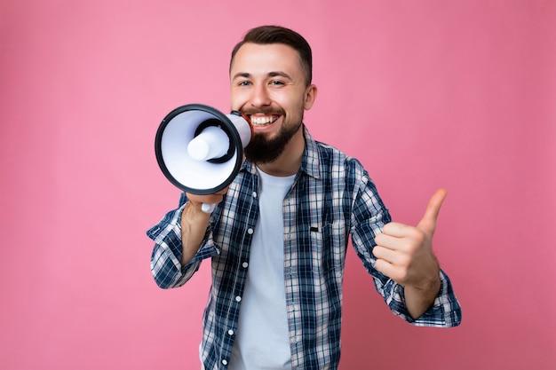 Фотография молодого красивого позитивного счастливого улыбающегося брюнет с бородой и искренними эмоциями.