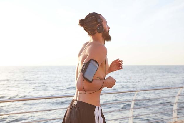 若いハンサムなスポーティなひげを生やした男の写真、ヘッドフォンで新しいクールな音楽を聴き、海辺で走っています。朝と夕焼けをお楽しみください。