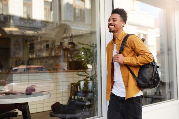 Фотография молодого счастливого афроамериканца в желтой рубашке, идущего по улице, слушая любимую песню в наушниках, выглядит веселым, наслаждается солнечным днем в городе и широко улыбается.