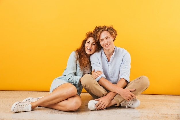 若い幸せなカップルの男性と女性が一緒に床に座って、黄色の背景で隔離の笑顔と抱擁の写真