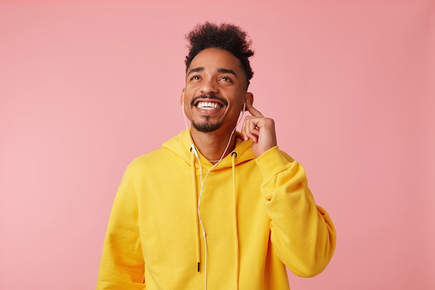 黄色いパーカーを着た若い幸せな暗い肌の男の写真、ヘッドフォンで彼のお気に入りの曲を楽しんで、夢のように見上げて、立って、広く笑顔。