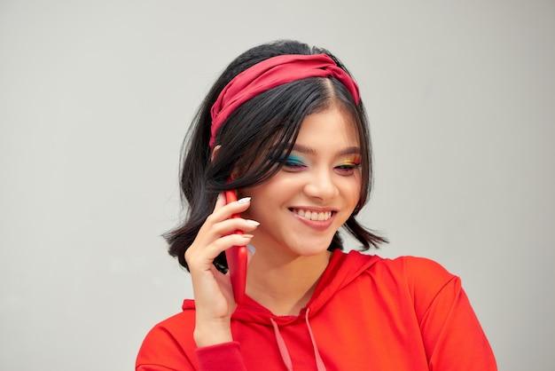 携帯電話で話している灰色の背景の上に孤立して立っている若い幸せな女性の写真
