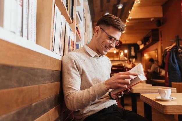 Фотография молодого счастливого человека, сидящего в кафе, читая книгу и глядя в сторону.
