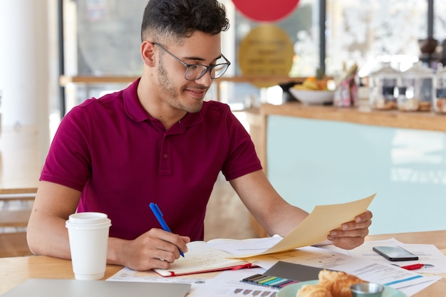 경험이없는 젊은 기업가의 사진은 비즈니스 문서의 정보를 메모장에 기록하고, 그래픽과 차트를 연구하고, 투자자에게 정보를 제공하고, 커피를 마실 준비를합니다.