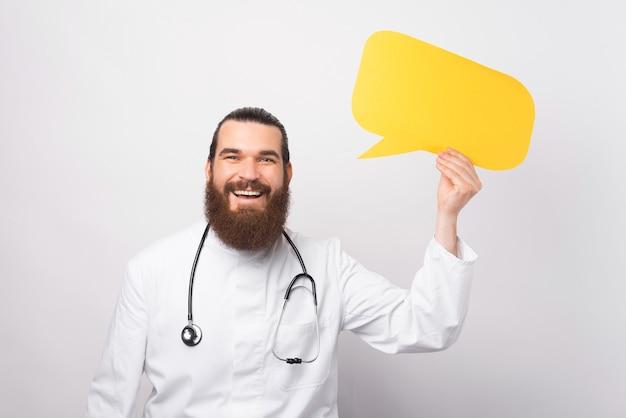 Фотография молодого радостного доктора, стоящего на белом фоне и держащего желтый речевой пузырь