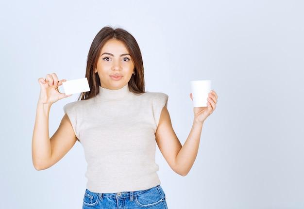 プラスチック製のコップとカードを手に持っている若い女性の写真。
