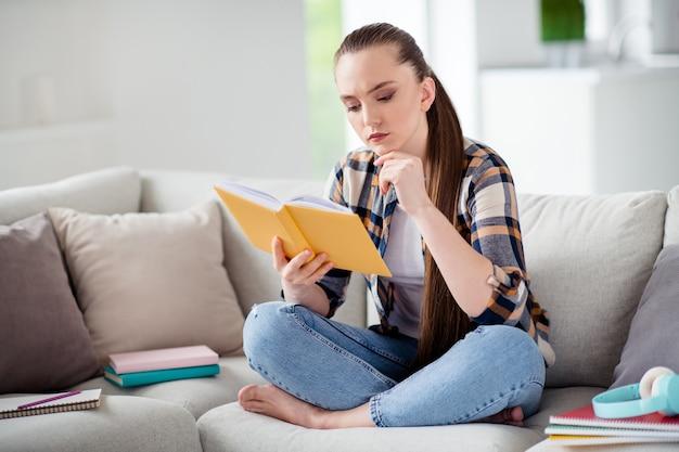 Фото молодой девушки студент держать книгу дневник руки сидеть диван ноги скрещенными мечтательно