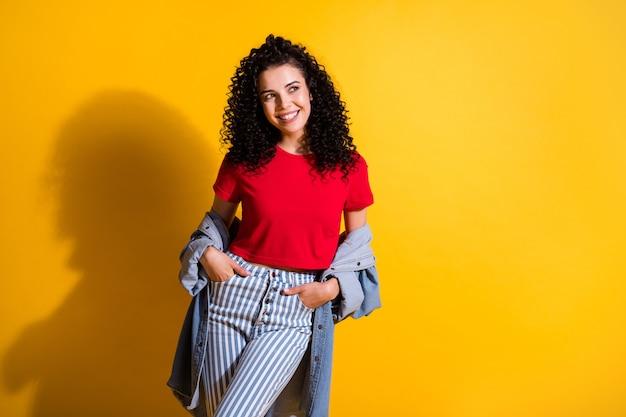 若い素敵な女性の手のひらのポケットの写真は空のスペースを着用してください赤いトップストライプジーンズジャケット分離された黄色の背景