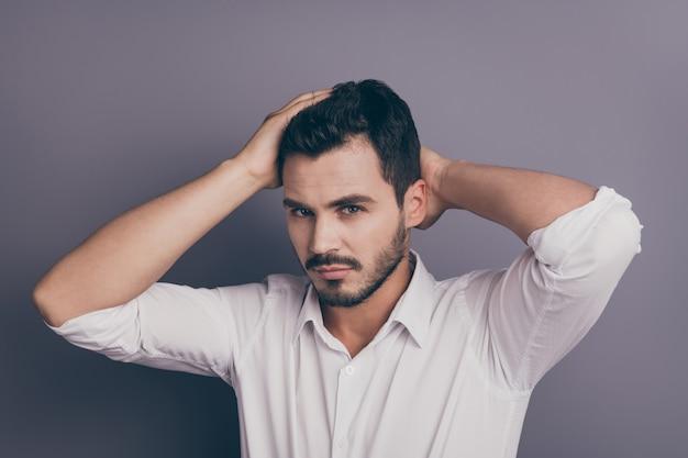 若いマッチョなビジネスマンの手が頭の髪型に触れる写真
