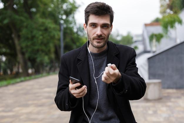 야외를 걷는 동안 휴대 전화를 들고 이어폰을주는 젊은 남자 20 대의 사진