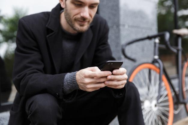 자전거와 함께 야외에 앉아있는 동안 휴대 전화를 사용하는 젊은 남자 20 대의 사진