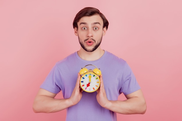 パステルカラーの背景の上に分離された若い男の驚いたショックを受けた驚きの遅い締め切り時計タイマーの写真