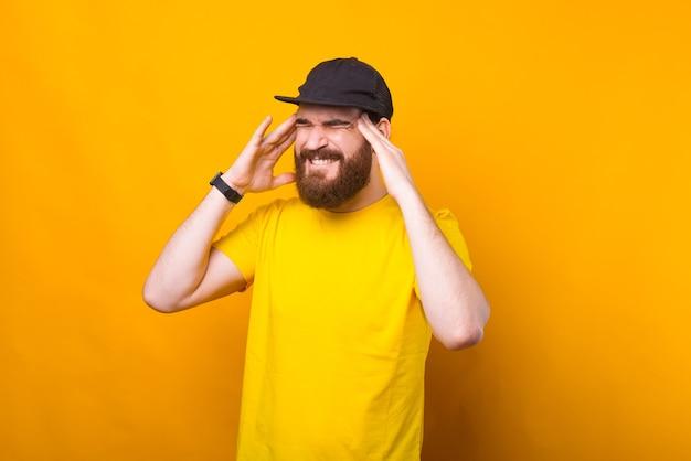 黄色い壁に頭痛を抱えている若い男の写真