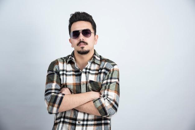 흰 벽에 서있는 검은 안경에 젊은 남자의 사진.