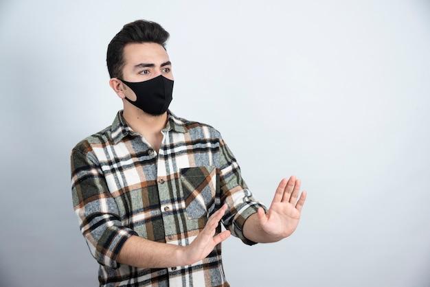 Фотография молодого человека в черной маске для защиты от коронавируса, стоящего над белой стеной.