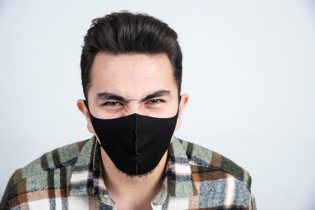 白い壁の上に立っている保護コロナウイルスのための黒いマスクの若い男の写真。