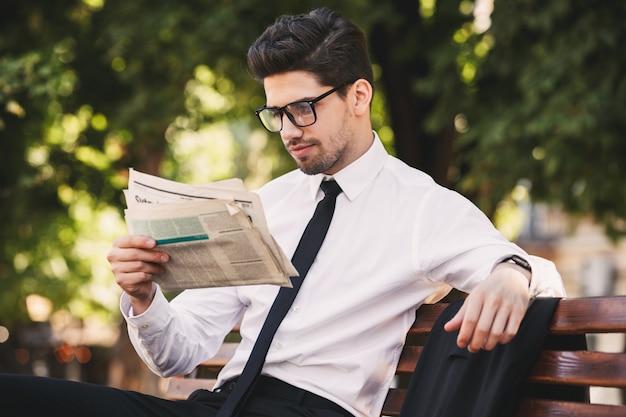 緑の公園のベンチに座って、晴れた日に新聞を読んでビジネスライクなスーツを着た若い男の写真