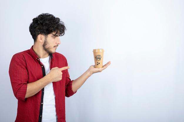 흰색 바탕에 커피 한잔에 가리키는 캐주얼 복장에있는 젊은 남자의 사진. 고품질 사진