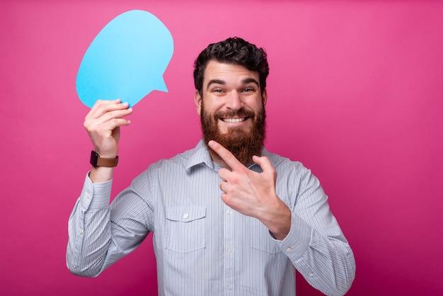 파란색 거품 연설을 캐주얼하게 가리키는 젊은 남자의 사진