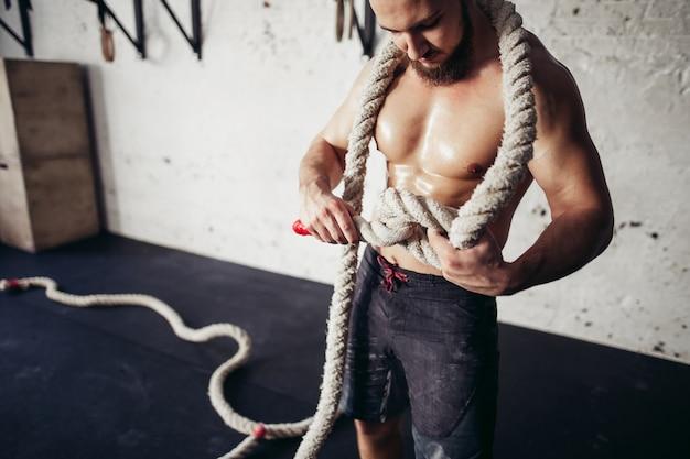 スポーツウェアの若い男の写真は結び目を編みます。強さと動機。