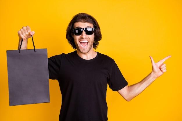 若い男の写真は、直接指の空きスペースホールドモールパッケージ口を開けたtシャツサングラス孤立した黄色の背景を示しています