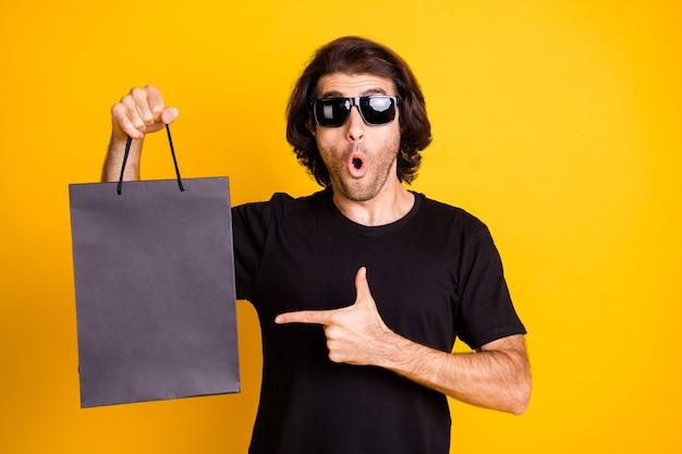 若い男の写真は、直接指モールバッグショックを受けた表現を示しています口を開けてtシャツサングラス分離された黄色の背景
