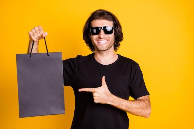 若い男の写真は、直接指店パケット晴れやかな笑顔のtシャツサングラス分離黄色の背景を示しています