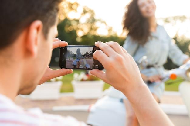 그녀는 도시 공원에서 오토바이에 앉아있는 동안 휴대 전화에 그의 여자 친구를 촬영하는 젊은 남자의 사진
