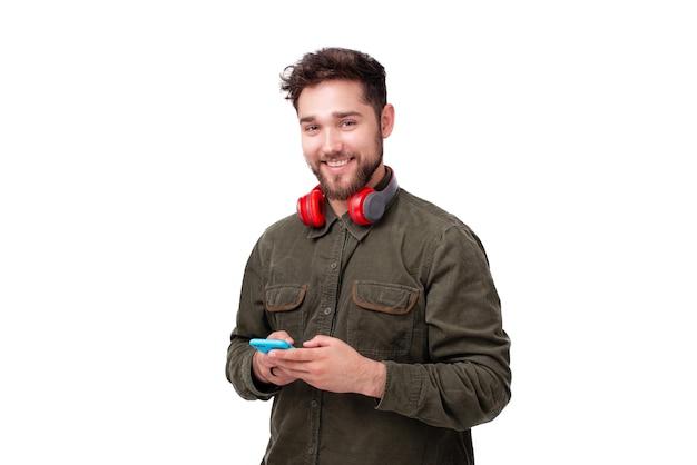 흰색 배경 위에 카메라를 즐겁게 보고 있는 동안 smaprtone을 사용하는 젊은 남자의 사진