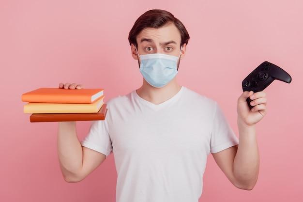 若い男の着用マスクの写真は、ピンク色の背景の上に分離された本を読むか、ビデオゲームの遠隔教育の家を再生する選択を決定します