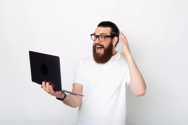 白い背景の上のラップトップに驚いてカジュアルに見えるひげを持つ若い男の写真