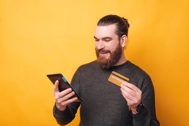 クレジットカードでオンラインで何かを購入するひげを持つ若い男の写真