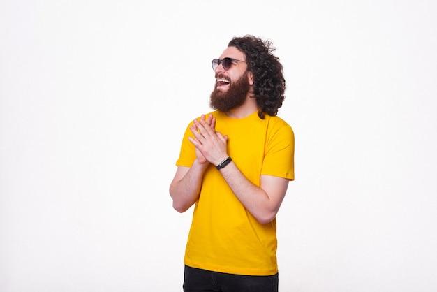 Фотография молодого человека с бородой в желтой футболке и смеющегося