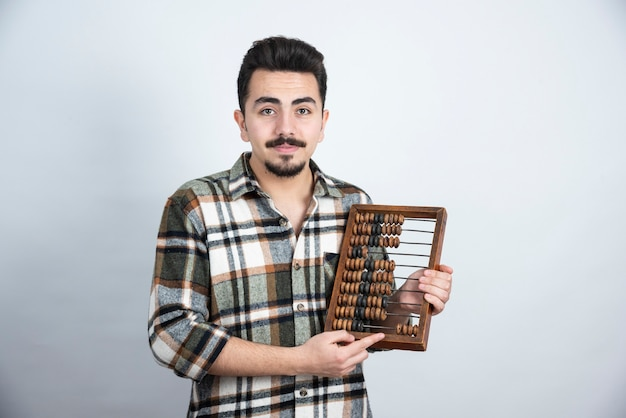 白い壁の上に立っている木製のカウントビーズを持つ若い男の写真。