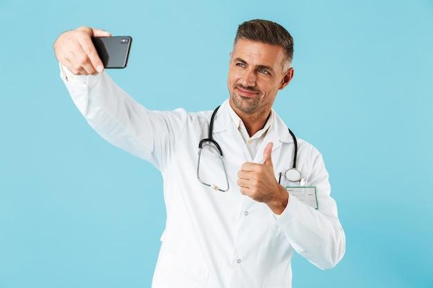 白衣と聴診器を身に着けている若い医師がスマートフォンで自分撮りをしている写真、青い壁の上に孤立して立っている
