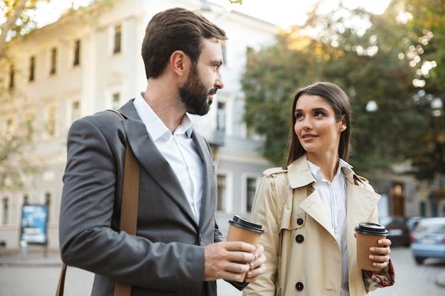 街の通りを歩きながら持ち帰り用のコーヒーを飲むフォーマルな服装の若いサラリーマンの男性と女性の写真