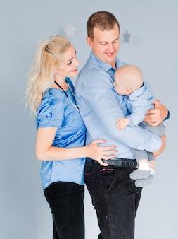 青色の背景に一緒にポーズの息子を持つ若い親の写真