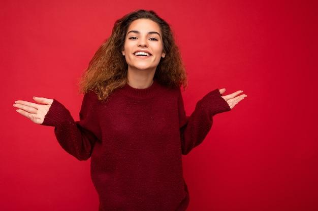 カジュアルを身に着けている誠実な感情を持つ若いポジティブ幸せな美しいブルネットの巻き毛の女性の写真
