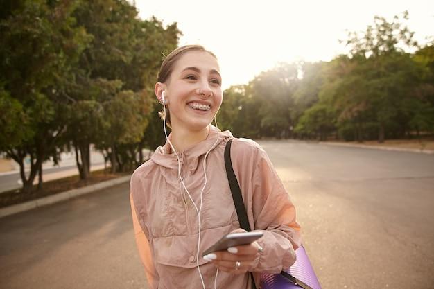 Фотография молодой позитивной дамы, идущей после йоги в парке, сжимающей смартфон в руке и болтающей с другом, слушающей музыку в наушниках, широко улыбаясь и отводящей взгляд