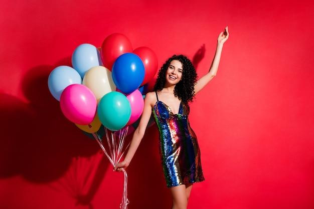 Фотография молодой красивой девушки держит много воздушных шаров, поднимает руку, носит глянцевое короткое платье, изолированное ярким красным цветом фона